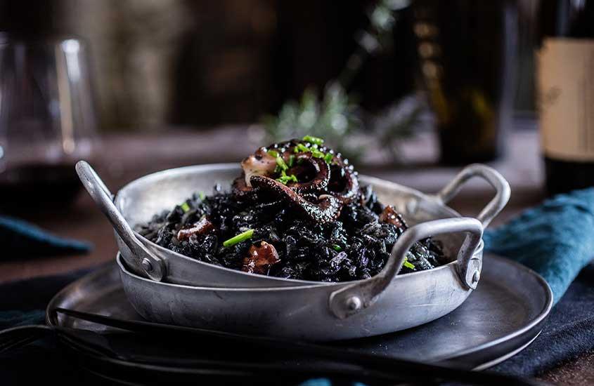 vasilha de alumínio redonda com risotto negro, um dos pratos da culinária croata que e leva lula, azeite, alho, vinho tinto