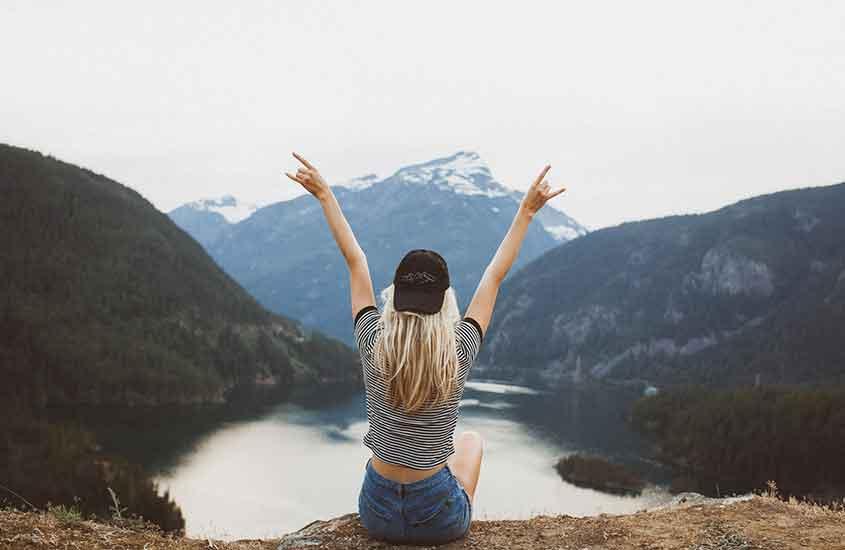 Viajante sentada de braços abertos em frente as montanhas, curtindo a paisagem