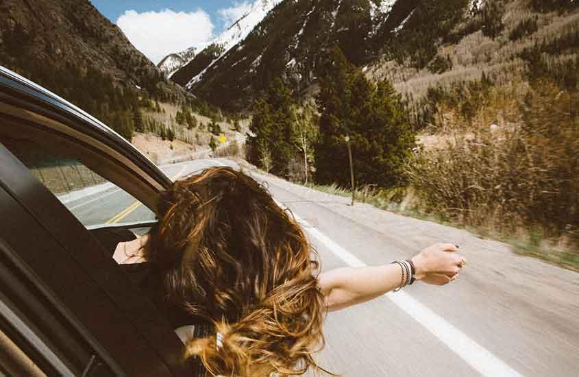 Viajante, com os braços e cabeça para fora da janela do carro, curtindo o vento. O que mostra, como viajar sozinha é bom