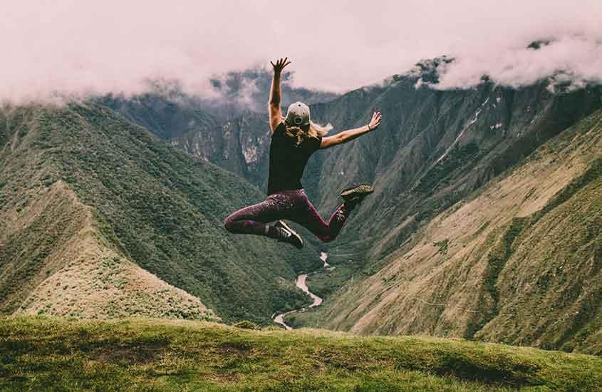 Mulher pula feliz com os braços abertos. O que mostra, como viajar sozinha é bom