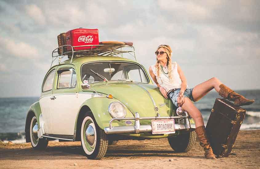 mulher sentada em fusca, com os pés apoiados em uma mala de viagem