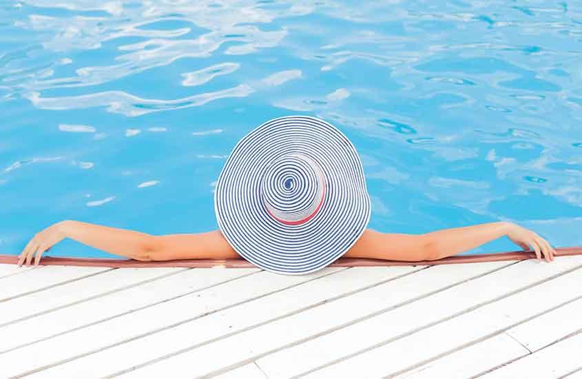 Mulher relaxando sozinha em piscina, o que mostra, como viajar sozinha é bom