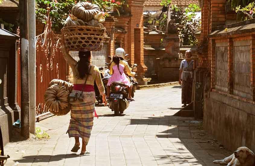mulher caminha carregando balde na cabeça em uma das ruas da Indonésia