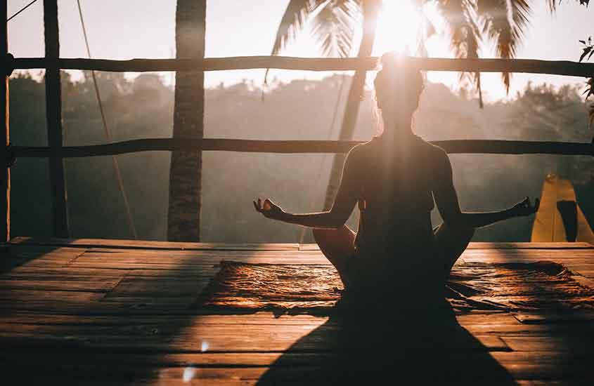 Mulher meditando durante o entardecer