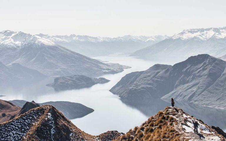 viajantes tiram fotos em cima de montanha com vista para o mar na nova Zelândia, durante o dia