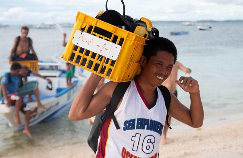 homem carrega caixa com equipamentos de mergulho