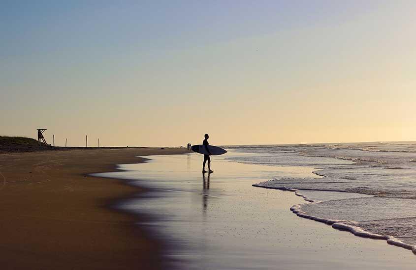 surfista em praia de Florianópolis, durante uma viagem solo em um dos melhores lugares para viajar sozinha no brasil