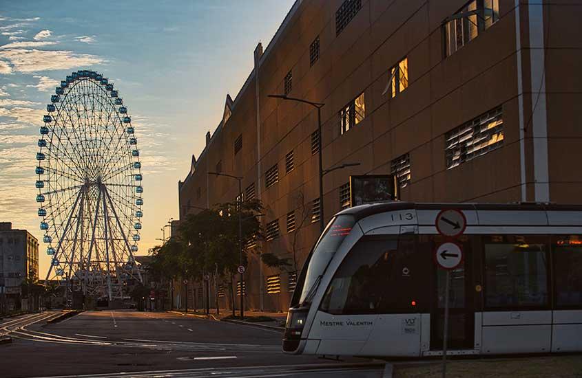 VLT, passa em trilhos, ao entardecer. Ao fundo, há a Rio Start, uma roda gigante que é uma atração interessante para quem busca o que fazer no centro do rio de janeiro