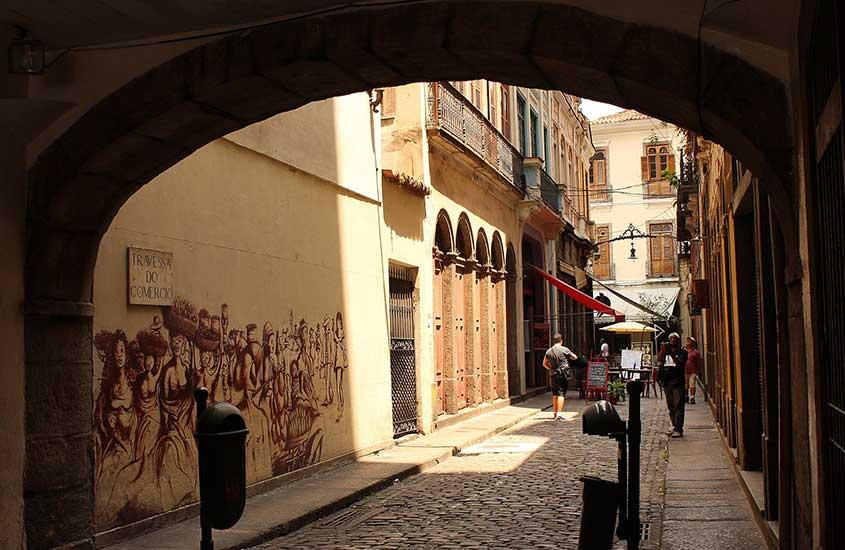 Pessoas caminham durante o dia em rua onde há o Arco do teles
