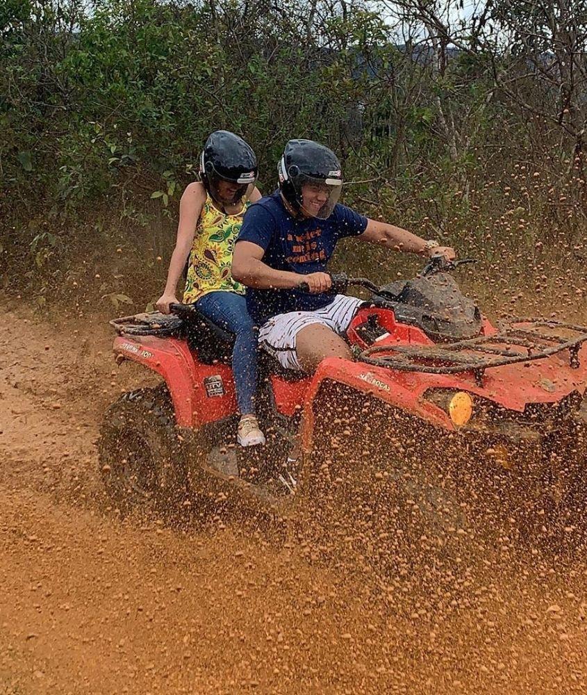 Pessoas andando de quadriciclo por pista de lama em Macacos MG