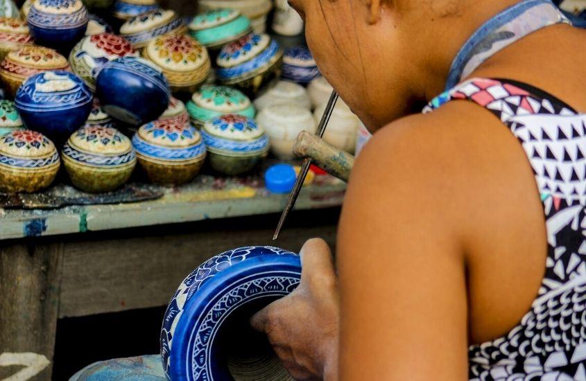 mulher pinta vaso de cerâmica em feirinha de artesanato que é um atrativo interessante para quem busca o que fazer em Macacos MG