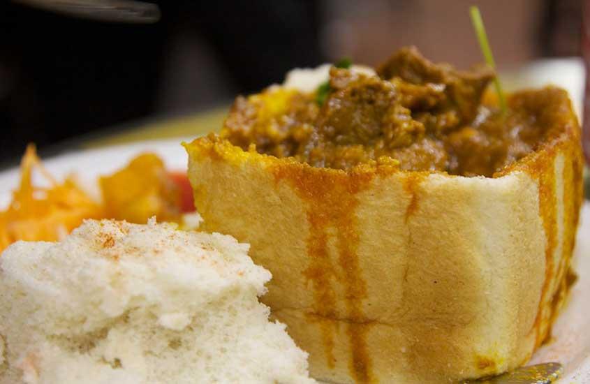 prato branco com pão vazado, recheado com curry picante, uma comida da África do sul