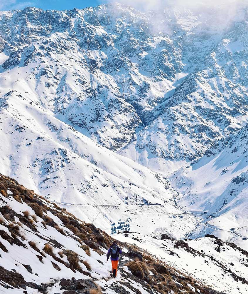 Homem caminha em montanha cheia de neve. Uma das curiosidades do Marrocos é que há tempestades de neve