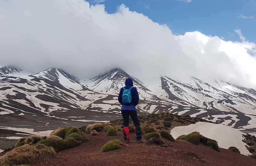 homem olha para montanha com neve no Marrocos