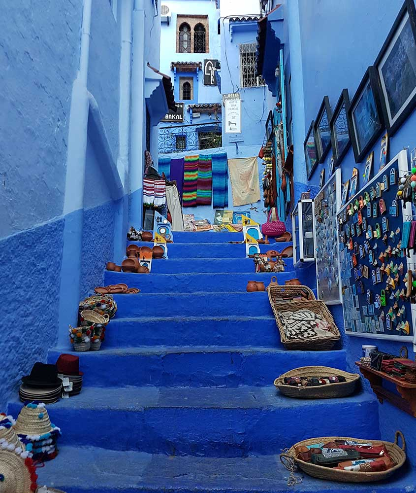 chapéus, quadros, cadeados em escada azul. Uma das curiosidades do Marrocos é que há uma cidade toda pintada de azul, conhecida como Chefchaouen