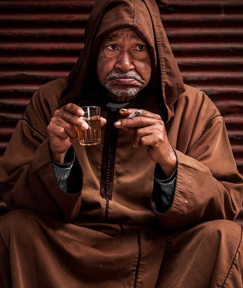 Homem segura copo de cerveja e cigarro. Uma das curiosidades sobre o Marrocos é que é difícil encontrar álcool