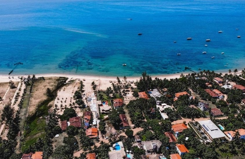 vista aérea de casas, areia e barcos no mar de Barra Grande, um dos lugares baratos para viajar na bahia