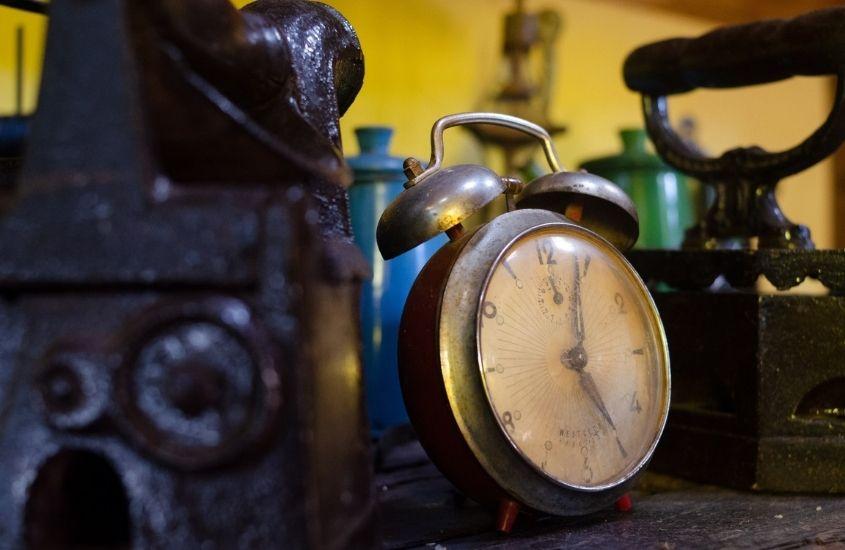 Relógio e ferramentas antigas em cima de mesa de madeira