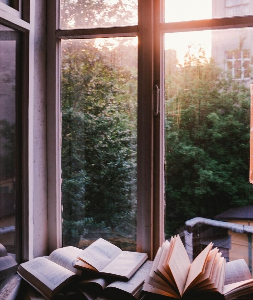 Livros em frente à janela com paisagem e pôr do sol