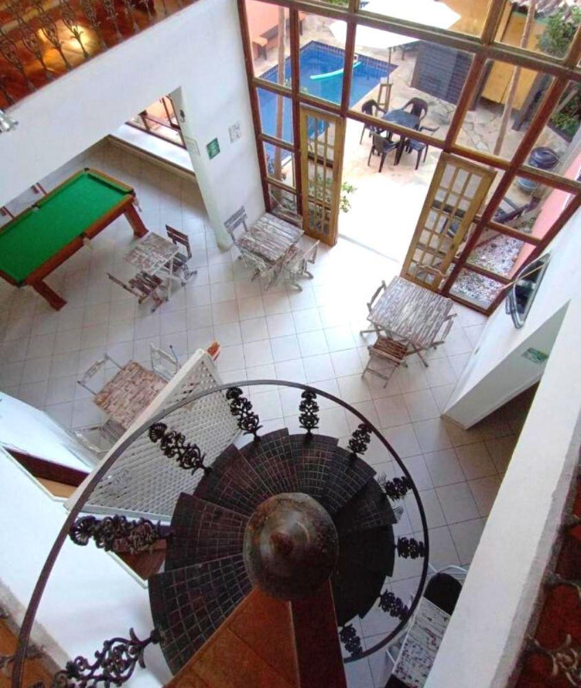 mesas, cadeiras e sinuca em sala de estar de Beluga, uma das melhores pousadas em búzios
