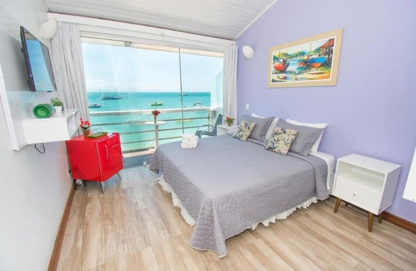 cama de casal, frigobar e televisão em quarto com vista para o mar de Bamboo Búzios Hostel