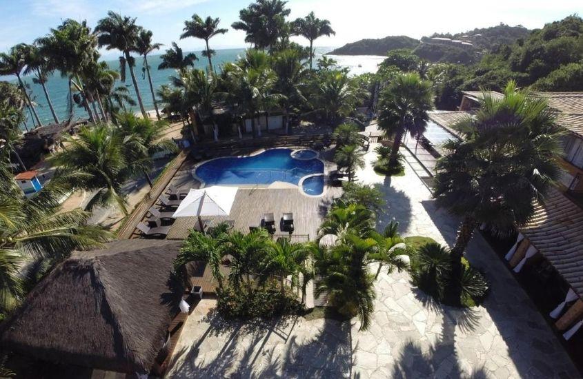 vista aérea de piscina e coqueiros em área de lazer de Rio Búzios Boutique, uma das melhores pousadas em búzios