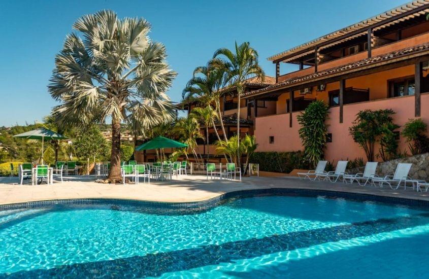 cadeiras e mesas em frente a piscina, em dia ensolarado em Piscina do Hotel Ferradura Resort em Buzios