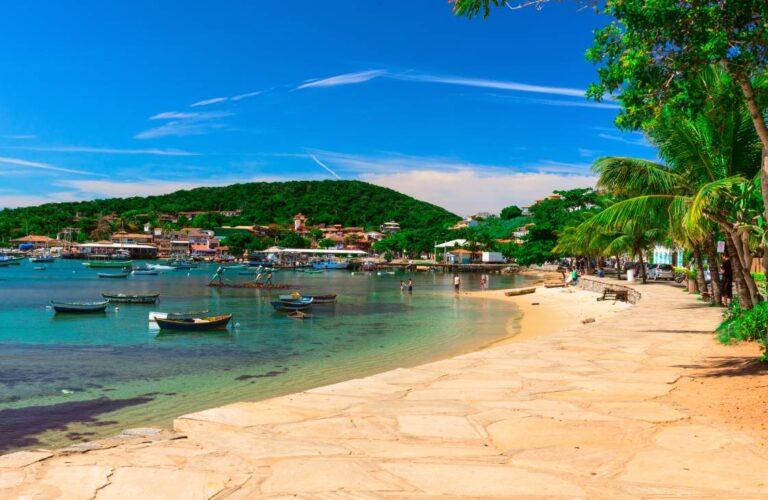 Praia em Búzios, barcos, vegetação e dia ensolarado