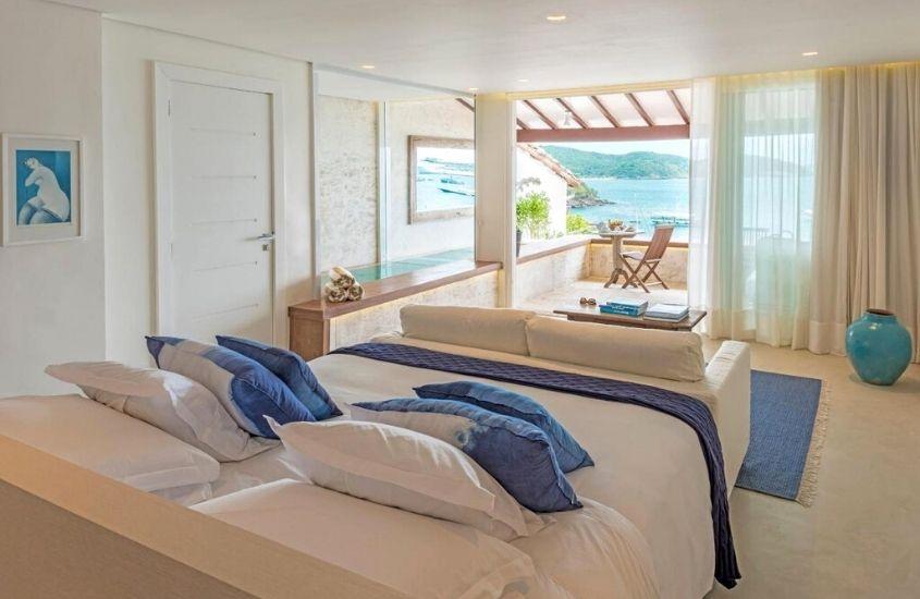 cama de casal, sofá, mesa e cadeira em quarto de hotel com vista para o mar em buzios