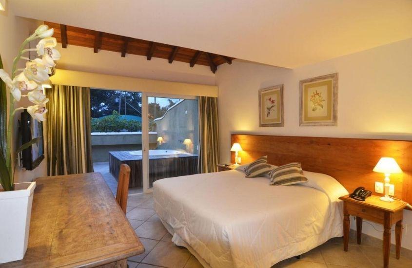 cama de casal, mesa e hidromassagem em quarto de Pousada dos Búzios, uma das melhores pousadas em búzios