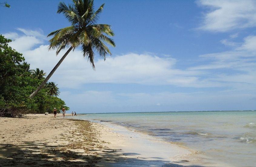 pessoas caminhando em areia de praia de Moreré, uma opção para quem busca o que fazer em Boipeba