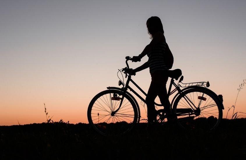 silhueta de mulher com bicicleta admirando o pôr do sol