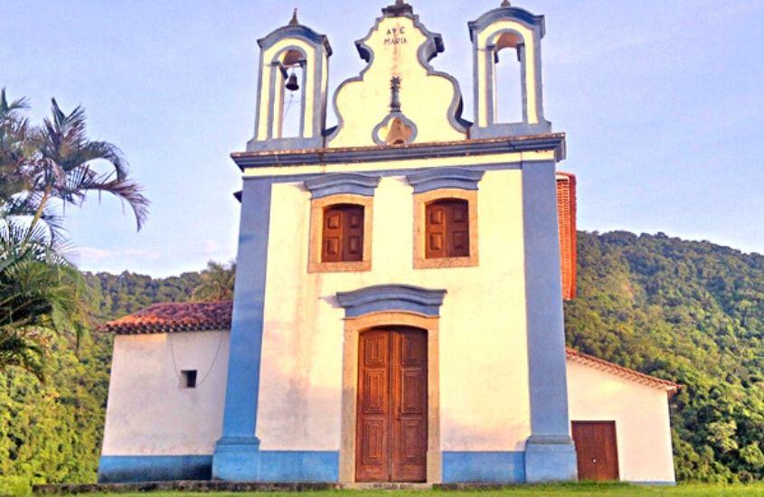 igreja branca e azul cercada de árvores em Vargem Grande rj