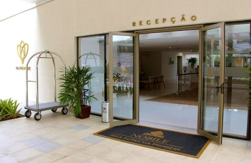 Plantas, tapete e porta de vidro aberta em entrada do hotel Nobile Inn Via Premiere