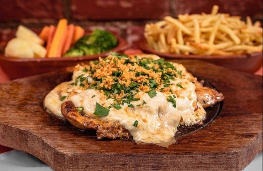 parmegiana, batata frita e salada em cima de mesa m restaurante Gepetto em Vargem Grande RJ