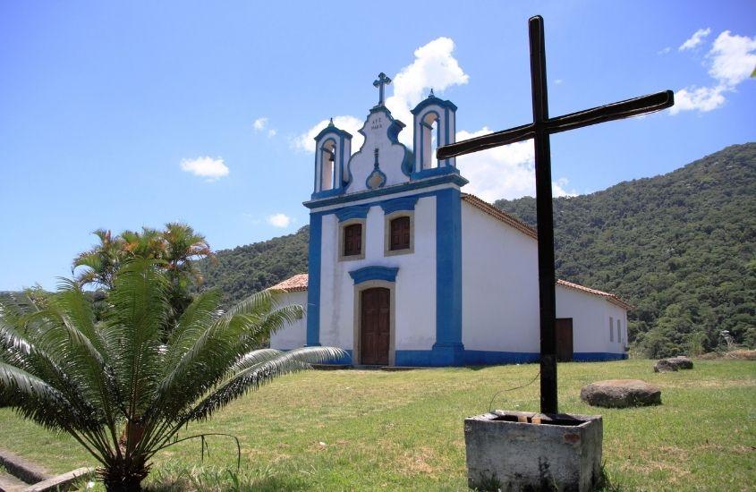Capela branca e azul de Nossa Senhora de Mont Serrat. Ao fundo, montanhas em vargem grande rj