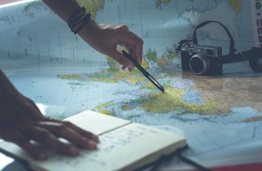 Pessoa anotando informações de mapa para planejar uma viagem