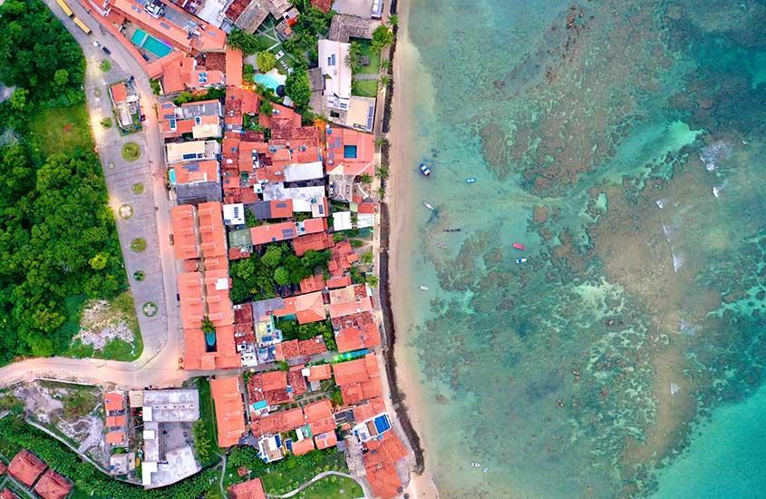 vista aérea de casas, vegetação e praia em morro de são Paulo, durante o dia