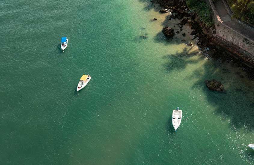 barcos em mar, durante o dia. Passeios de barcos são um dos melhores atrativos quem busca o que fazer em morro de são Paulo