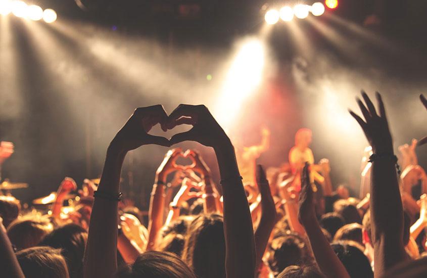pessoas fazem coração com as mãos em direção ao placo, durante um show em morro de Sao Paulo