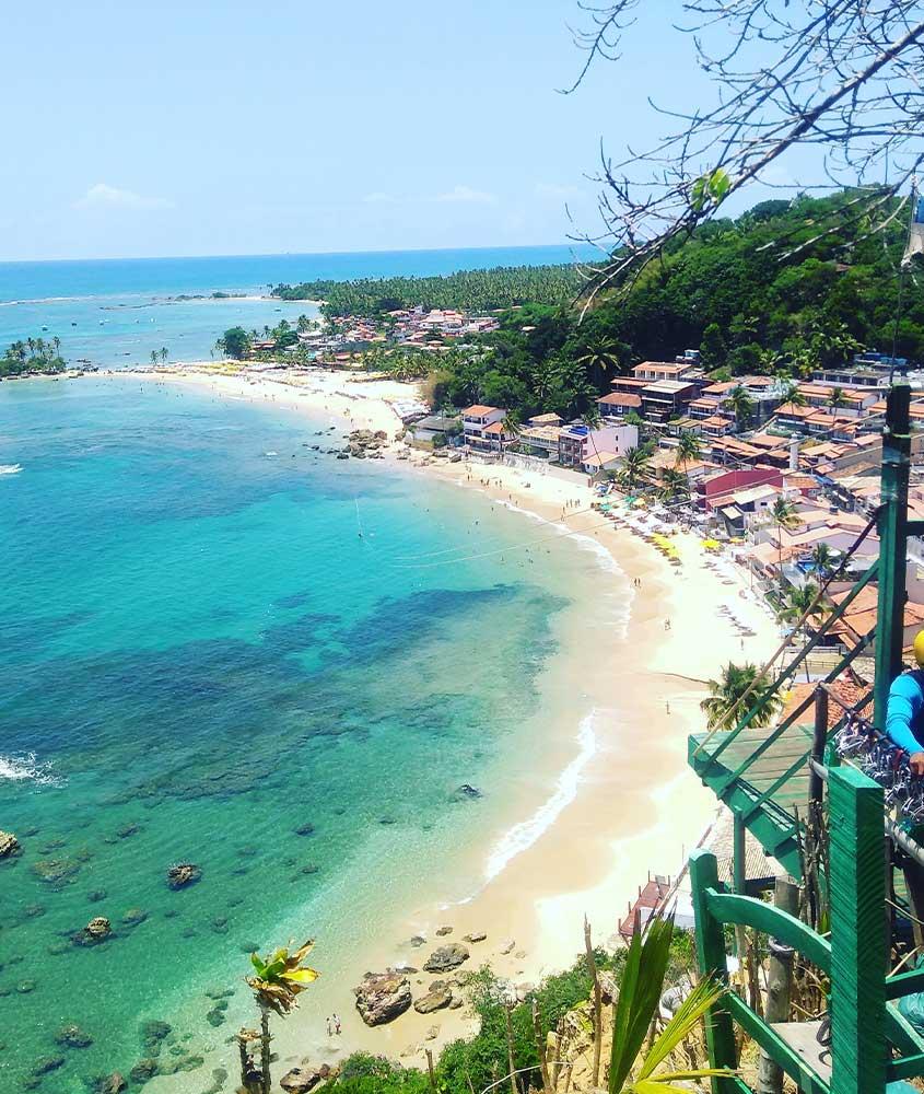 vista aérea de tirolesa sobre praia, uma ótima atração para quem busca o que fazer em morro de são paulo