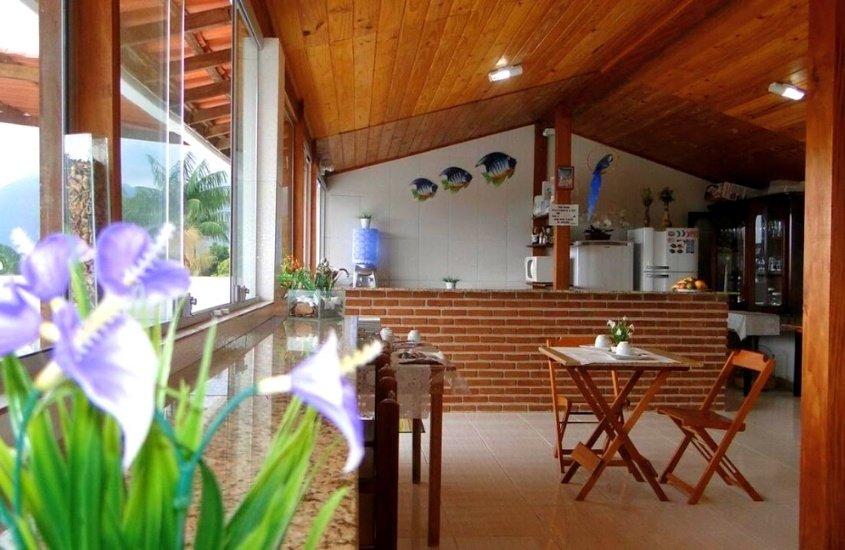 mesa e cadeiras de madeira, geladeiras e armário em cozinha de Encontro das Águas, uma das pousadas de trindade