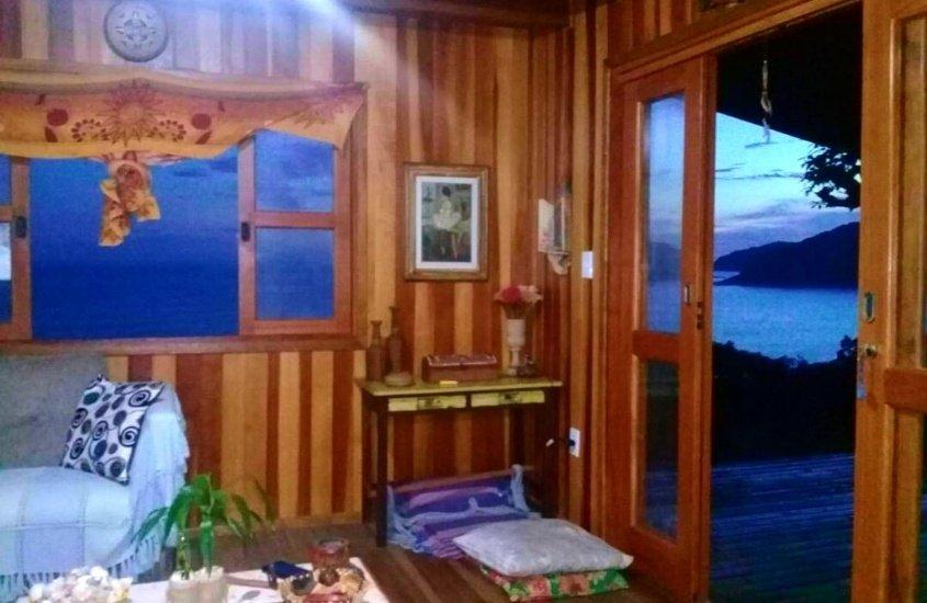 sofá em sala de Chalé da Sol com com vista para o mar em Trindade