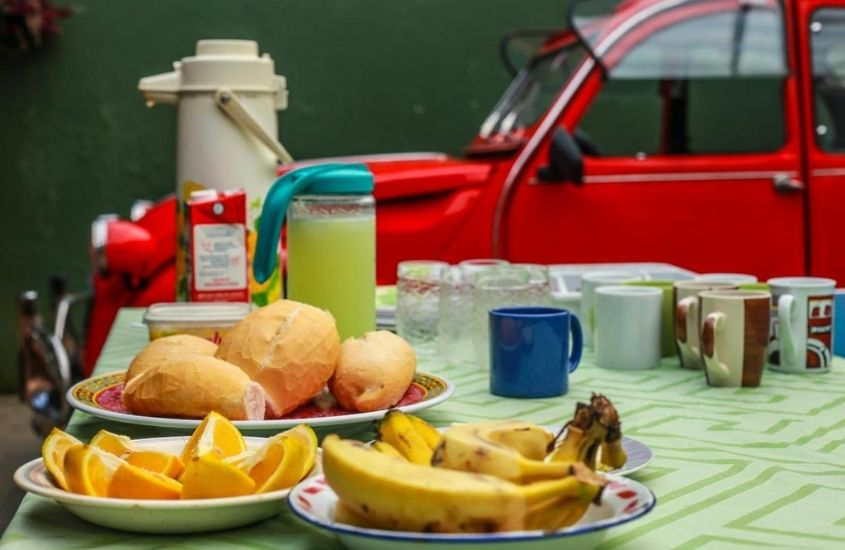 pães, frutas e sucos em mesa de café de Hostel Trindade, uma opção para quem busca onde ficar em Trindade