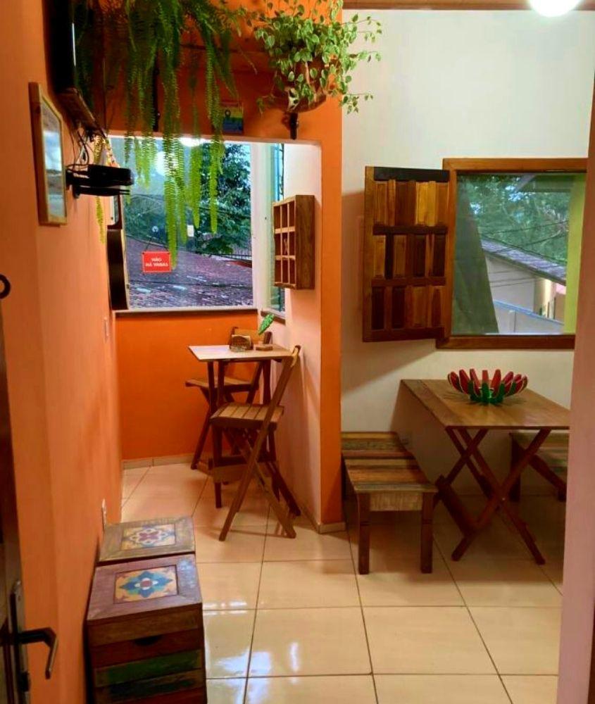 plantas, mesas e cadeiras de madeira em sala de Bicho Preguiça Hostel, uma opção para quem busca onde ficar em Trindade