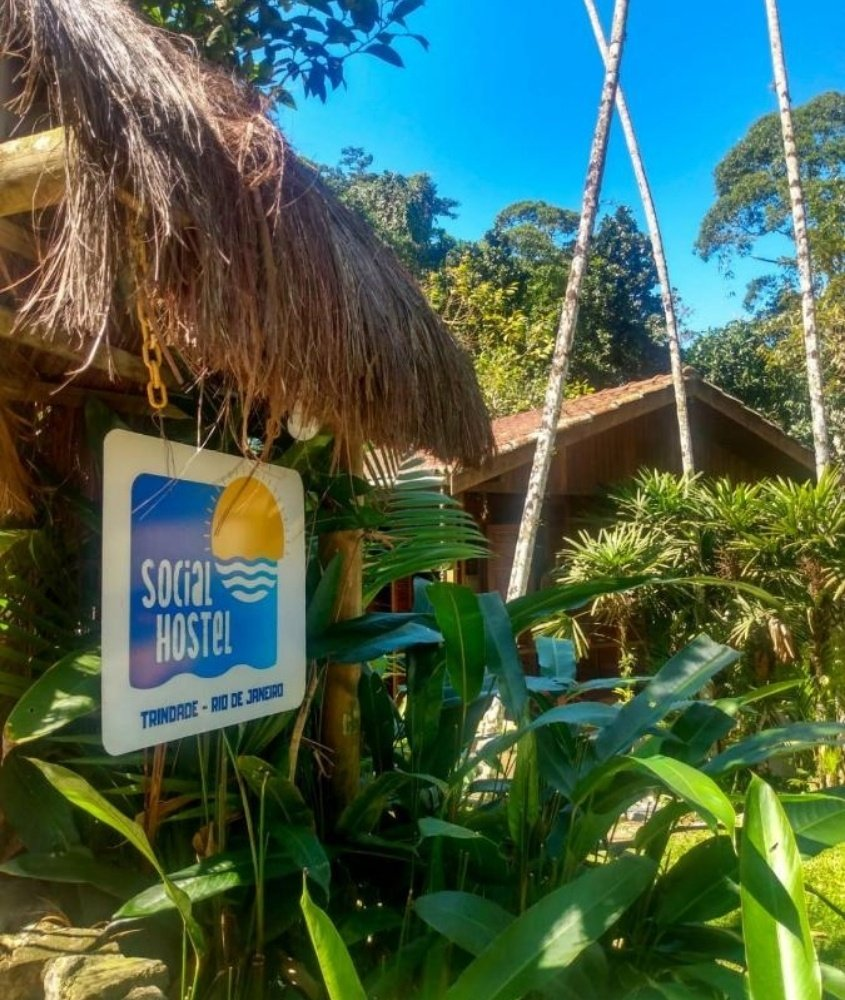 placa onde há escrito 'social hostel, trindade - rio de janeiro' pendurada em cabana