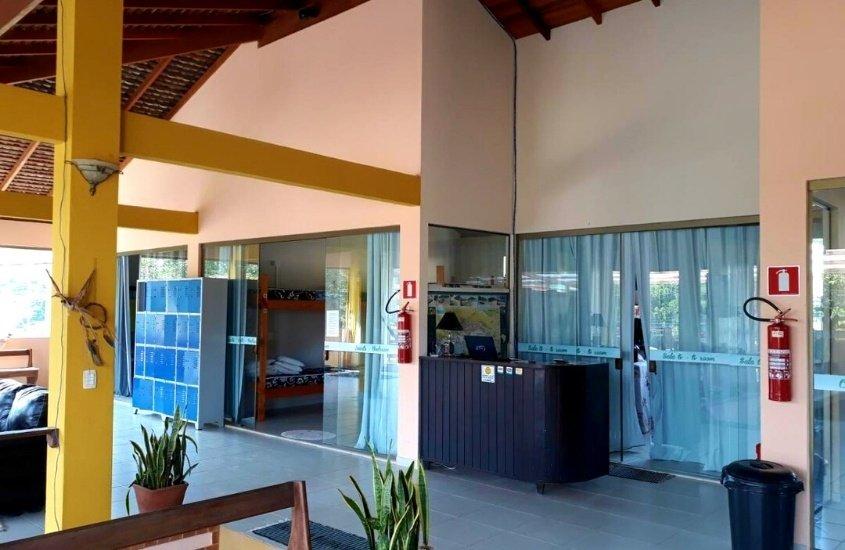 armários, sofá, plantas, banco, lixeira e balcão em recepção de Ti Hostel, uma opção para quem busca onde ficar em Trindade