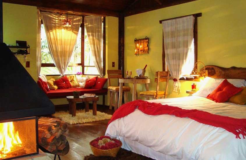 cama de casal, lareira, sofá e mesa em quarto de pousada dos Amores