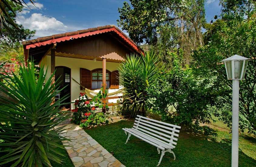 banco branco em frente a chalé em jardim de pousada sabor da terra, uma alternativa para quem busca onde ficar em Visconde de Mauá