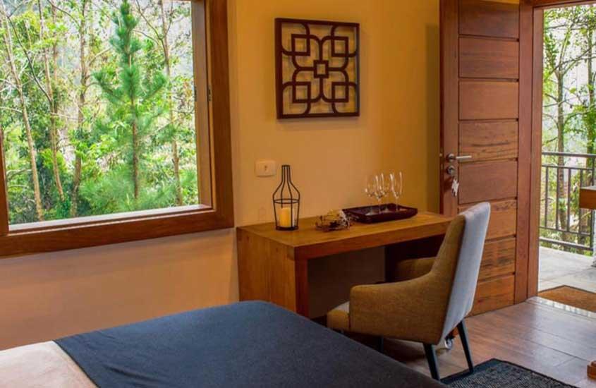 mesa, cadeira e cama em quarto de Chalé Realli, uma boa opção de pousada para quem busca onde ficar em Visconde de Mauá